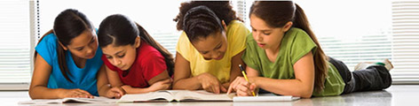 Four young girls on the floor doing homework